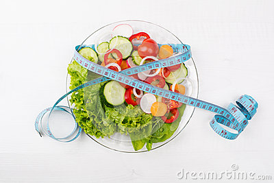 Plate with fresh vegetables salad and measured tape isolated on