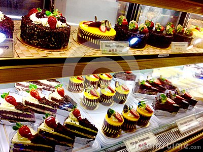 stock image of tempting bakery fancy sweet chocolate cakes desserts mango cheesecake & fresh strawberries