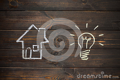House and bulb drawn on wooden boards. Drawing with chalk.