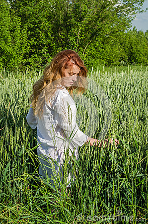 Young charming woman walking outdoors in a field near the green bushes and trees, hand patting wheat ears, dressed in a beautiful