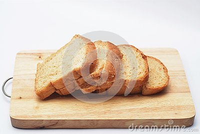 Four slices of bread on the wooden cutting board in white background.