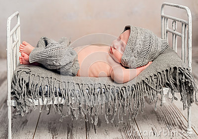 Newborn baby in knitted hat and pants sleeping on old cot