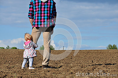 Happy loving family. Father and his daughter child girl playing and hugging outdoors in the field. Cute little girl hugs daddy.