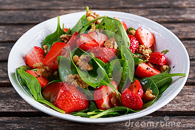 stock image of summer fruit vegan spinach strawberry nuts salad. concepts health food