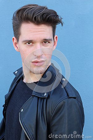 Fashion man, Handsome serious beauty male model portrait wearing leather jacket, young guy over blue background
