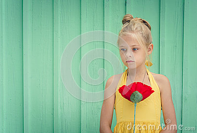 Sad young blond girl holding a red flower