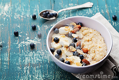 Bowl of fresh oatmeal porridge with banana, blueberries, almonds, coconut and caramel sauce on teal rustic table