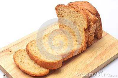 The cut loaf of bread on the wooden cutting board on the white background.