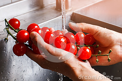 Man's hands washing tomatoes.