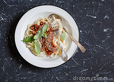 Spaghetti with vegetarian lentil bolognese on a dark background.