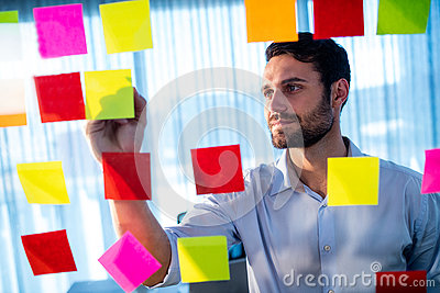 Businessman writing on post it