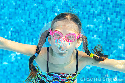 Child swims in pool underwater, girl in goggles has fun under water and makes bubbles