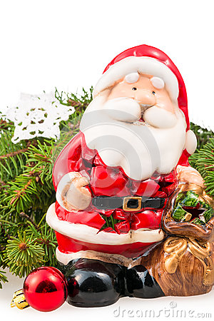 Figurine of Santa Claus near the branch of a Christmas tree