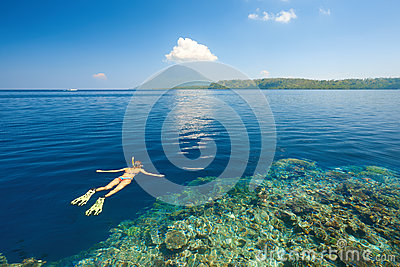 Woman snorkeling in clear tropical waters on a background of isl