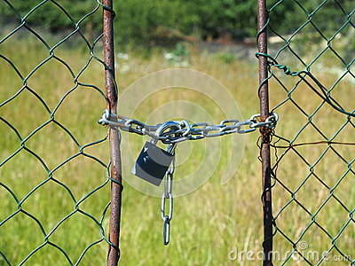 Wire netted fence locked by metail chain and padlocked