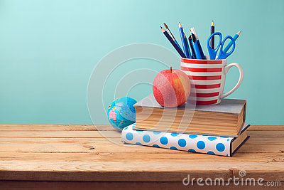 Back to school concept with books, pencils in cup, apple, and globe