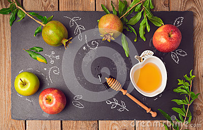 Jewish holiday Rosh Hashana background with apples, pomegranate and honey on blackboard. View from above.