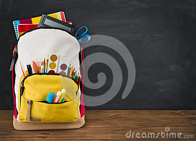 Backpack full of school supplies over black school board background