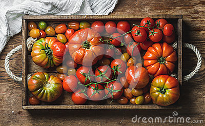 Colorful assortment of heirloom, bunch and cherry tomatoes in rustic tray over wooden background