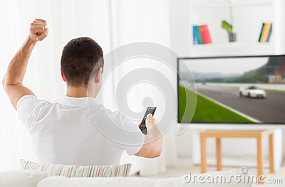 Man with remote watching motorsports on tv at home