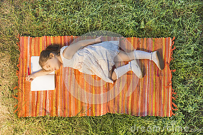 Little girl sleeping on the opened notebook lying down on the picnic blanket