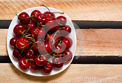 Plate with red cherries on wooden plates, top view, space for text