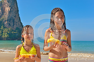 Happy kids on beach family vacation, children eating pineapple tropical fruit