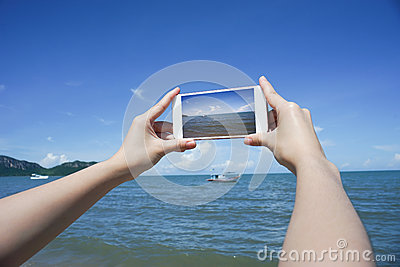 Close up of woman's hand holding smart phone, mobile, smart phone over blurred beautiful blue sea and fishing boat