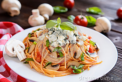 Spaghetti pasta salad with tomato sauce, mushrooms, blue cheese