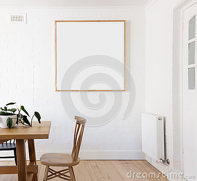 Blank framed print on white wall in danish styled interior dinin