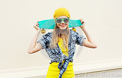 Fashion portrait pretty cool smiling girl with skateboard over white