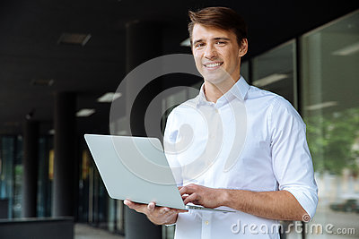 Happy businessman holding and using laptop