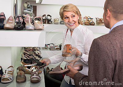Two retirees together choosing pair of shoes in fashion store