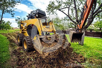 mini bulldozer working with earth, moving soil and doing landscaping works