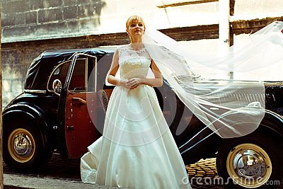Bride's veil spreads over a retro car while she stands behind it