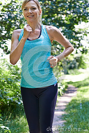 Mature Woman Running Outdoors In Countryside