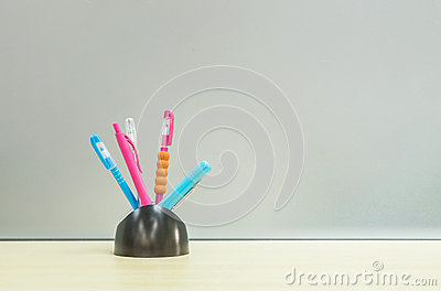 Closeup color pen with black ceramic desk tidy for pen on blurred wooden desk and frosted glass wall textured background in the