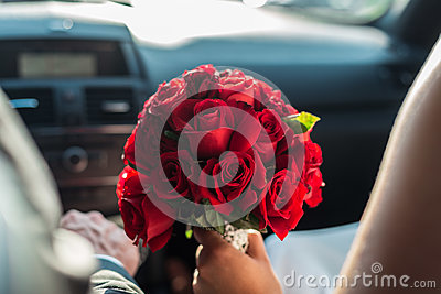 A detail shot of a beautiful bridal bouquet of red roses, held by the bride