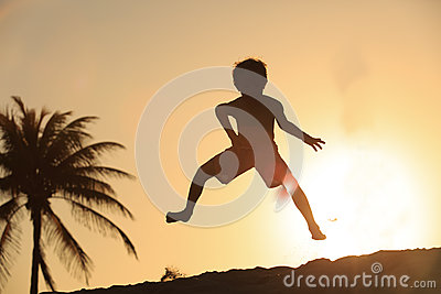 Happy little boy jumping at sunset beach