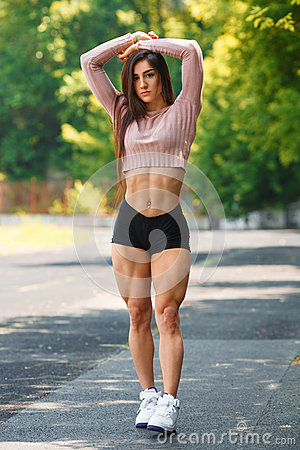 Beautiful muscular girl posing outdoor. Sexy athletic woman with big quads