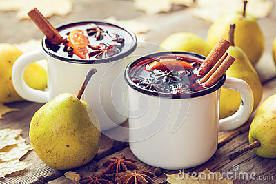 Mulled wine in white rustic mugs with spices and pear