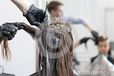 A hairdresser coloring hair of a female client