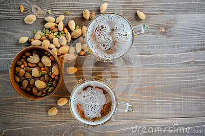 Two Oktoberfest beers with pistachio nuts on a wooden table