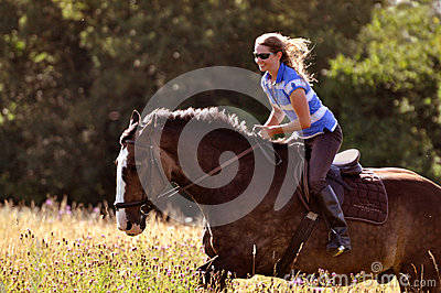Girl riding horse in meadow