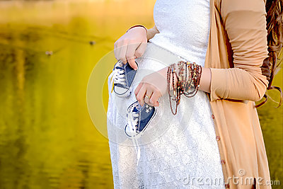 Pregnant woman belly holding baby booties. Healthy pregnancy.