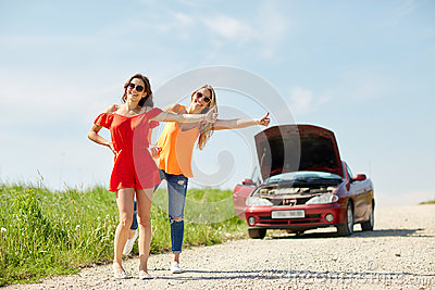 Women with broken car hitchhiking at countryside
