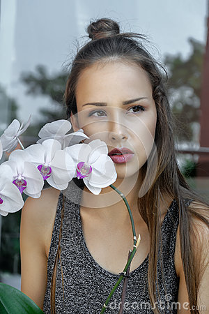 Girl with orchid flower is very sad.