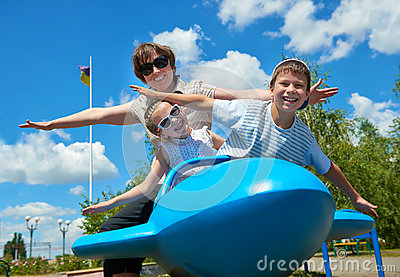 Child and woman fly on blue airplane attraction in park, happy family having fun, summer vacation concept