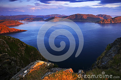 Sea landscape in the Norway. Evenig pink light on the ocean coast. Rocky cost in the summer night. Water surface with beautiful li