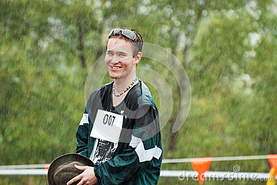 Handsome young Australian man sporting competitor caught in rain